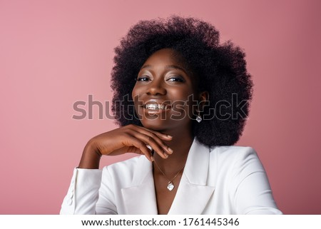 Yong beautiful happy smiling African American woman, model wearing elegant jewelry, white blazer, posing in studio, on pink background. Close up portrait. Copy, empty space for text