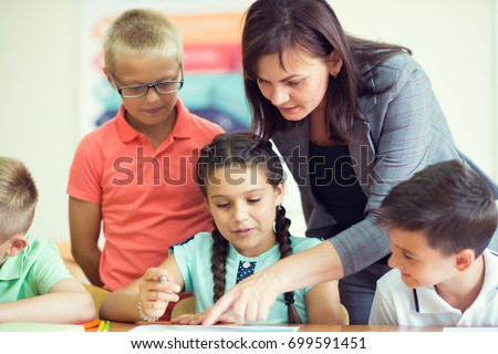 Yong beautiful teacher with group of clever children in school at classroom #699591451