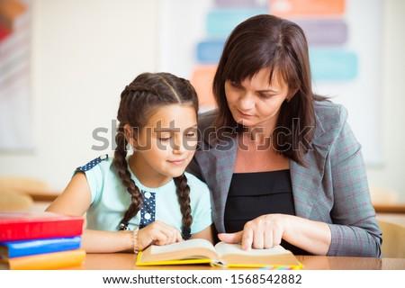 Yong beautiful teacher with schoolgirl school at klassroom