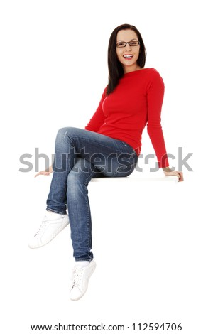 Yong casual woman sitting on something