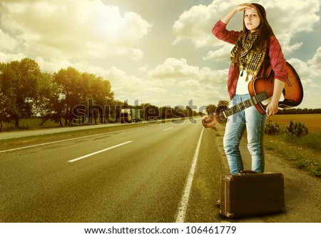Yong Girl  with guitar and old suitcase at the highway in sunset time