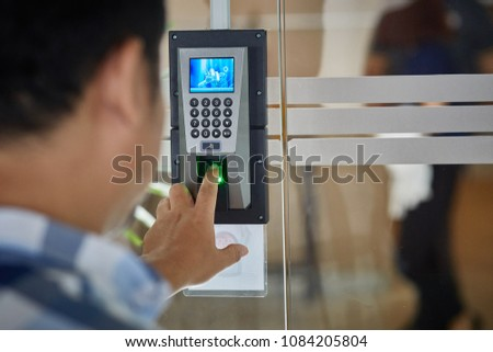 Yong man push finger down on the electronic control machine to access the door