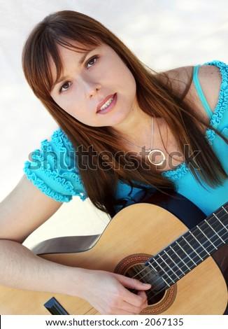 Yong pretty woman playing the guitar