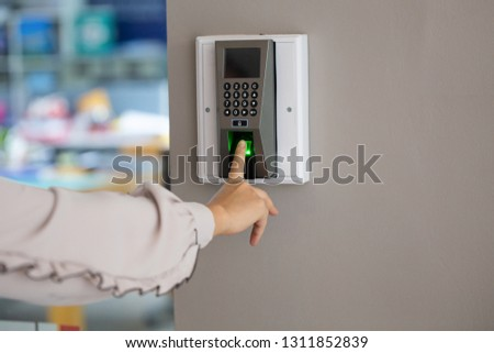 Yong working woman push finger down on the electronic control machine to access the door.
