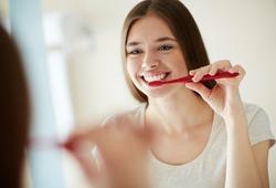 Yooung woman brushing her teeth at mirror
