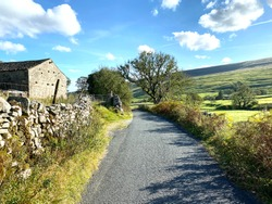 Yorkshire dales, country lane, with dry stone walls, old farm buildings, and hills in the distance near, Halton, Gill, Skipton, UK