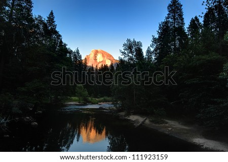 Yosemite National Park at Sunset: the light of the setting sun catches the top of half Dome and is reflected in the Merced River on the valley floor