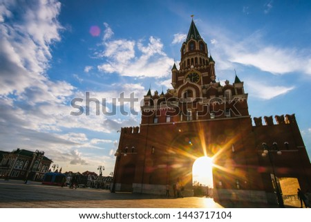 Yoshkar-Ola city, Republic of Mari El, Russia - May, 2019: View of the Spasskaya Tower on Bruges embankment in sunset rays #1443717104