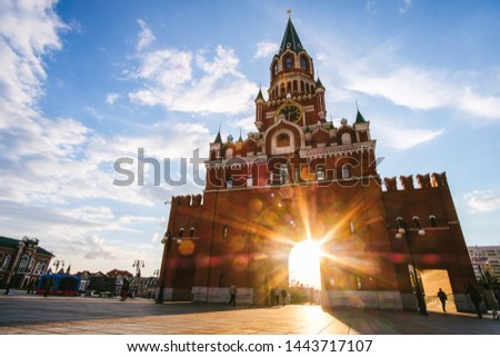 Yoshkar-Ola city, Republic of Mari El, Russia - May, 2019: View of the Spasskaya Tower on Bruges embankment in sunset rays #1443717107