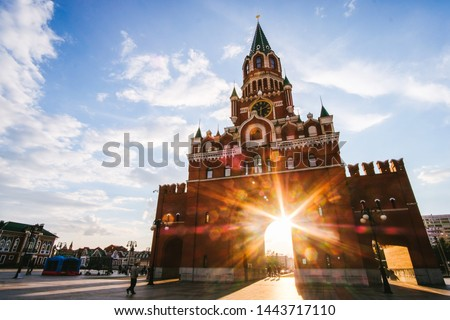 Yoshkar-Ola city, Republic of Mari El, Russia - May, 2019: View of the Spasskaya Tower on Bruges embankment in sunset rays #1443717110