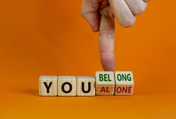 You alone or belong symbol. Businessman turns cubes and changes words you alone to you belong. Beautiful orange background. Business, psychology and you alone or belong concept. Copy space.