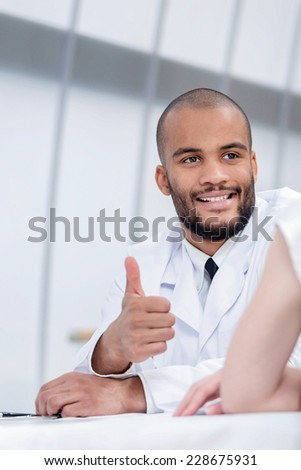 You are all well. Smiling doctor talking to patient while sitting at a table in the hospital. On the table, the doctor is a tablet and an x-ray of the patient. Doctor showing thumb up