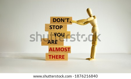 You are almost there symbol. Wooden blocks with words 'dont stop you are almost there'. Wooden model of human. Beautiful white background, copy space. Business and almost there concept. Foto stock ©