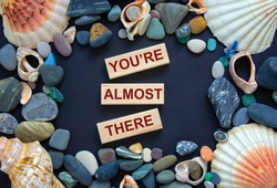 You are almost there symbol. Words 'You are almost there' on wooden blocks on a beautiful black background. Sea stones and seashells. Business and you are almost there concept.