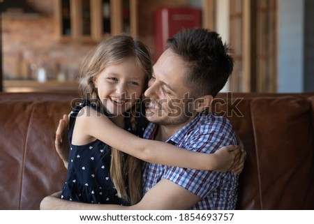Photo of  You are my best friend, daddy! Cute tender little girl spending free time on weekend with beloved millennial father embracing him tight laughing talking joking together sitting on couch at living room