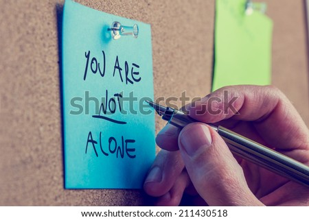 You Are Not Alone man writing an inspirational message on a blue sticky note pinned to a cork board with a fountain pen