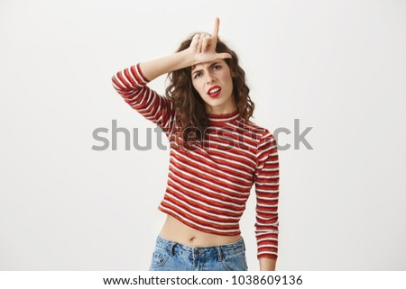 You are outsider. Studio shot of annoyed good-looking woman, feeling cool and confident while tilting head and showing loser-sign over forehead, standing with disrespectful expression over gray wall #1038609136