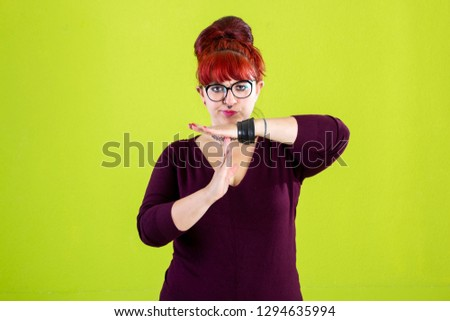 You are outsider. Studio shot of annoyed good-looking woman, feeling cool and confident while tilting head and showing loser-sign over forehead #1294635994