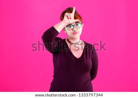 You are outsider. Studio shot of annoyed good-looking woman, feeling cool and confident while tilting head and showing loser-sign over forehead #1333797344