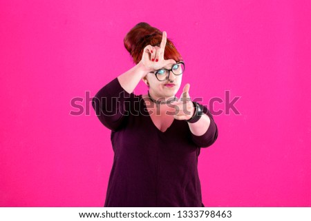 You are outsider. Studio shot of annoyed good-looking woman, feeling cool and confident while tilting head and showing loser-sign over forehead #1333798463