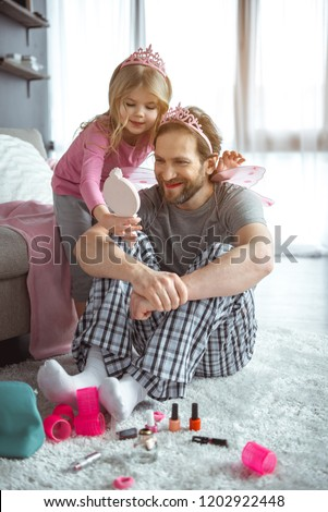 You are pretty fairy. Satisfied girl is showing mirror to her daddy after doing make-up. Man is looking at reflection with joy and laughing while sitting on floor in apartment