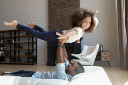 You are so strong, daddy! Excited active little black preteen girl playing with millennial dad flying in air stretching arms and legs while father lying on sofa holding daughter in arms lifting her up