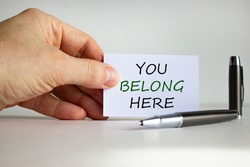 You belong here symbol. White paper with words 'You belong here' in businessman hand, metalic pen. Beautiful white background. Business, inclusion and you belong here concept. Copy space.