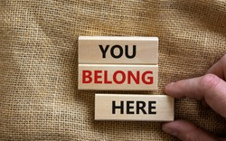 You belong here symbol. Wooden blocks with words 'You belong here' on beautiful canvas background. Male hand. Diversity, business, inclusion and belonging concept.