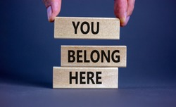 You belong here symbol. Wooden blocks with words 'You belong here' on beautiful grey background. Male hand. Diversity, business, inclusion and belonging concept.