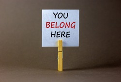 You belong here symbol. Wooden clothespin with white paper. Words 'you belong here'. Beautiful grey background. Business and you belong here support concept, copy space.