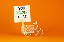 You belong here symbol. Wooden clothespin with white paper. Words you belong here. Miniature white bicycle. Beautiful orange background. Business and you belong here support concept, copy space.