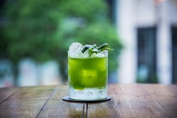 you can see a cocktail called gin basil smash standing on a table whose green color is strong and has a blurry background