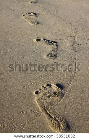 you can see the traces of an human foot in the sand of a beach