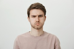 You disappointed me. Indoor portrait of handsome unshaven young man sulking and frowning eyebrows, being offended with cruel words, standing against gray background. Son waits for apology