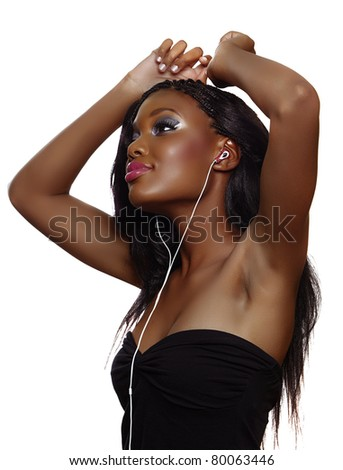 You happy South African woman with beautiful makeup listening to music on earphones over white background and dancing