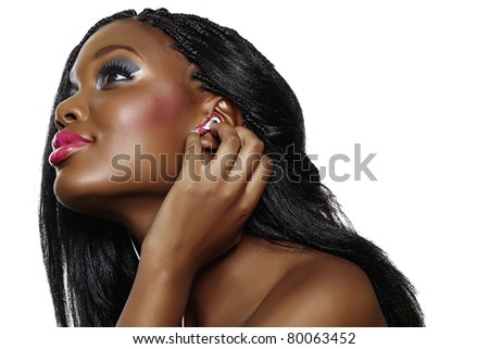 You happy South African woman with beautiful makeup listening to music on earphones over white background
