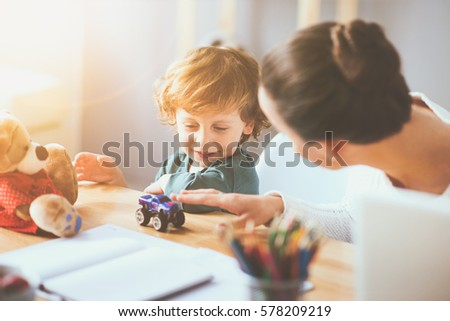 You make me happy. Delighted young thoughtful mother playing with her little child using toys and sitting at the table.