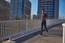 You man running over a bridge with tall buildings in the background