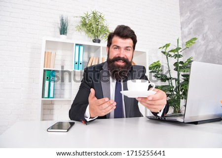 You need some caffeine. Happy hipster serve coffee in office. Director hold hot cup at desk. Caffeine energy. Caffeine addiction. Caffeine wakes you up. Morning drink. Breakfast tea.