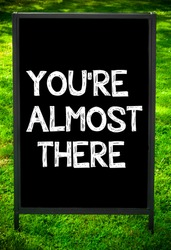 YOU'RE ALMOST THERE  message on sidewalk blackboard sign against green grass background. Copy Space available. Concept image