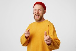 You're chosen bro. A young attractive interesting unusual guy dressed in a yellow sweater and a red hat winks with one eye, his finger points to the camera, encouraging, an approving gesture.