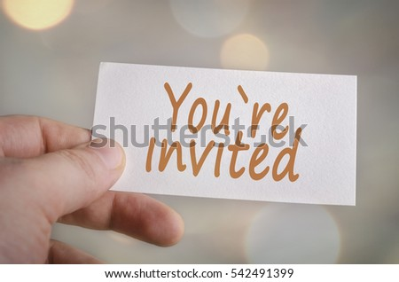 You`re invited card in hand with blurred bokeh lights in the background #542491399