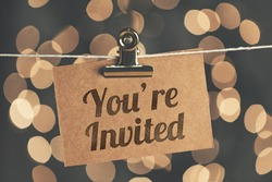 You're invited sign pegged to a string with blurred bokeh lights in the background
