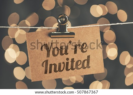 You're invited sign pegged to a string with blurred bokeh lights in the background #507867367