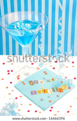 You\'re invited spelled out with cut out letters on blue napkin with blue martini with confetti and curled ribbons great for party invitations
