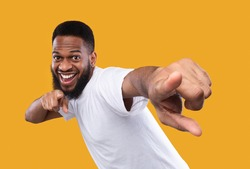 You're next. Funny african man pointing fingers at camera posing in studio on yellow background. I choose you concept, advertisement banner with cheerful black guy
