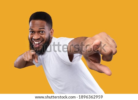 You're next. Funny african man pointing fingers at camera posing in studio on yellow background. I choose you concept, advertisement banner with cheerful black guy Stock photo ©