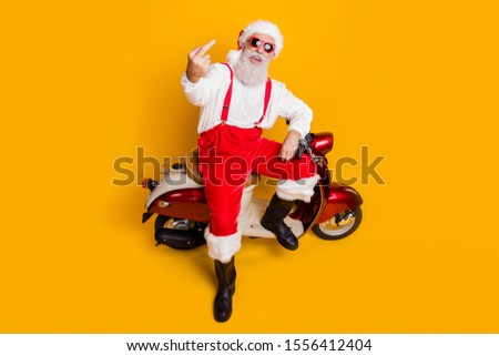 You're outsider! Full body high angle view photo of crazy santa sitting bike showing impolite gesture wear sun specs pants cap shirt boots isolated yellow color background
