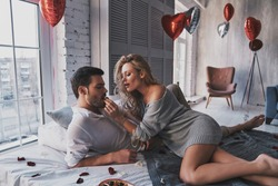 You should try it.  Beautiful young couple eating chocolate candies and drinking champagne while lying on the bed at home