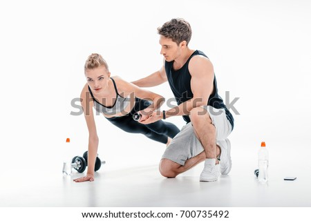 yougn girl doing exercise with trainer isolated on white